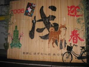 材木が並べられたところに犬の絵が塗装されている