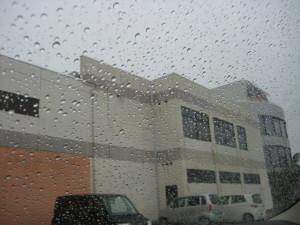 車のフロントガラスに雨のしずく。奥はアラピア。